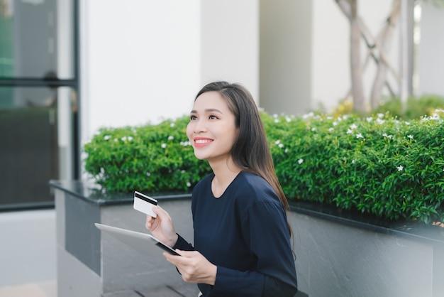 Kobieta zakupy w internecie online z komputerem typu tablet i kartą kredytową