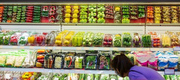 Kobieta zakupy w supermarkecie dla zdrowia półka na zakupy warzyw i owoców na jedzenie w supermarkecie.