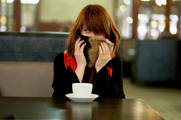 Kobieta zamarza w kawiarni, ogrzewa się filiżanką gorącego napoju