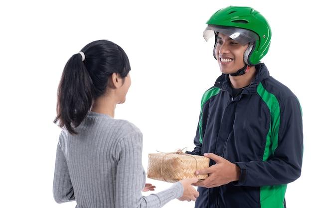 Kobieta zamawiająca jedzenie online dostarczane przez kuriera w mundurze na białym tle