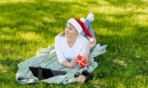 Kobieta zamawiania prezentów na laptopie i picia kawy. szczęśliwa kobieta kupuje prezenty świąteczne online. dziewczyna robi zakupy online na komputerze. surfowanie i zakupy. wesołych świąt i szczęśliwego nowego roku