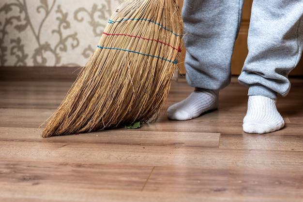 Kobieta zamiatanie podłogi miotłą