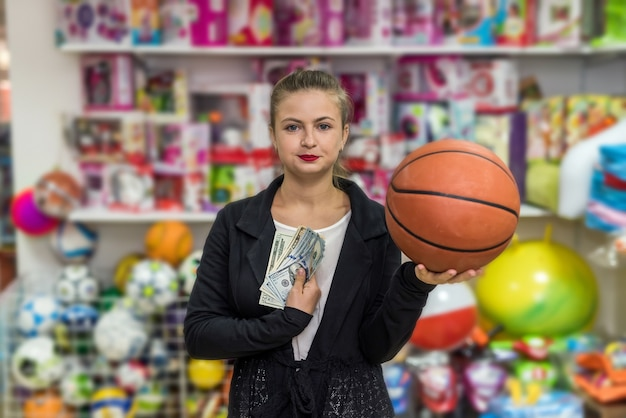 Kobieta zamierza kupić pomarańczową piłkę na prezent