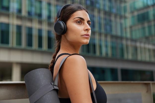 Kobieta zamierzająca ćwiczyć jogę na świeżym powietrzu idzie do studia gimnastycznego uprawia samotnie sport w centrum miasta podczas kwarantanny wraca do aktywności fizycznej po samoizolacji słucha popularnej muzyki