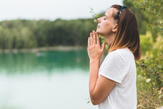Kobieta zamknęła oczy, modląc się na zewnątrz. ręce złożone w modlitwie o wiarę, duchowość i religię