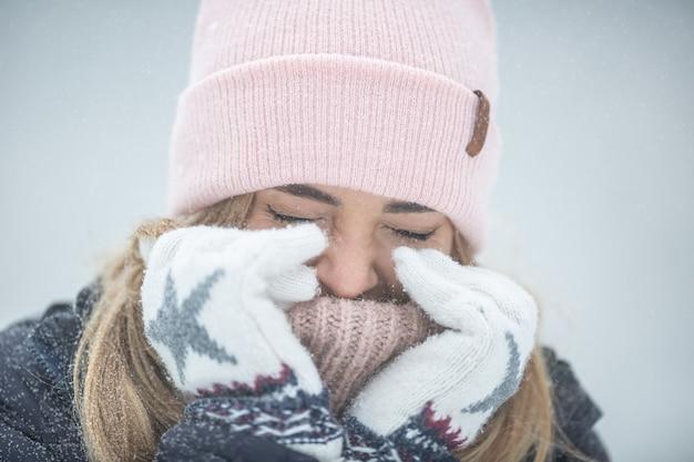 Kobieta zamyka tu oczy i rozgrzewa ręce w bardzo zimny dzień.