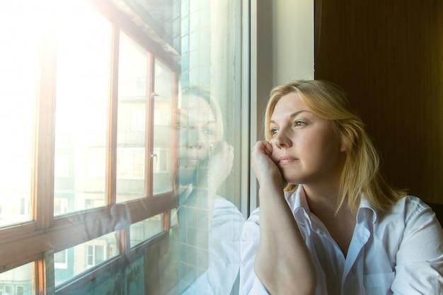 Kobieta zamyślona, wyglądająca przez okno.