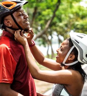 Kobieta zapina kask rowerowy dla swojego chłopaka