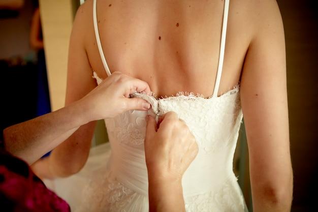 Kobieta zapinana na suknię ślubną