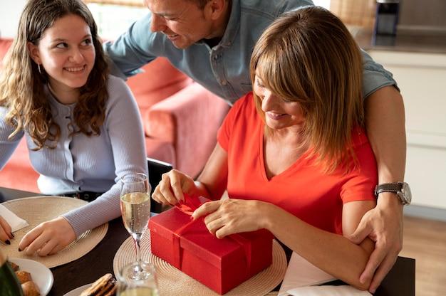 Kobieta zaskoczona prezentem na rodzinnym spotkaniu