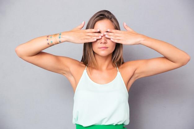 Kobieta zasłaniając oczy rękami