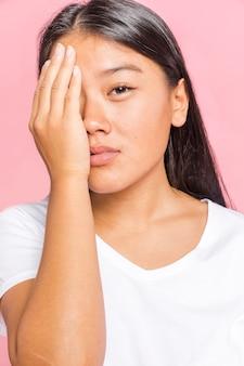 Kobieta zasłaniając twarz jedną ręką