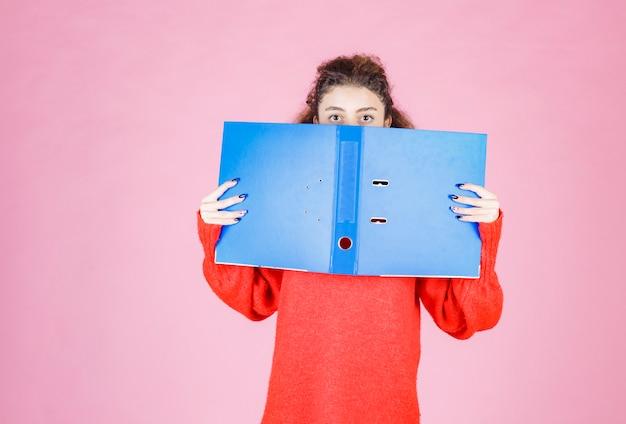 Kobieta zasłaniając twarz niebieskim folderem.