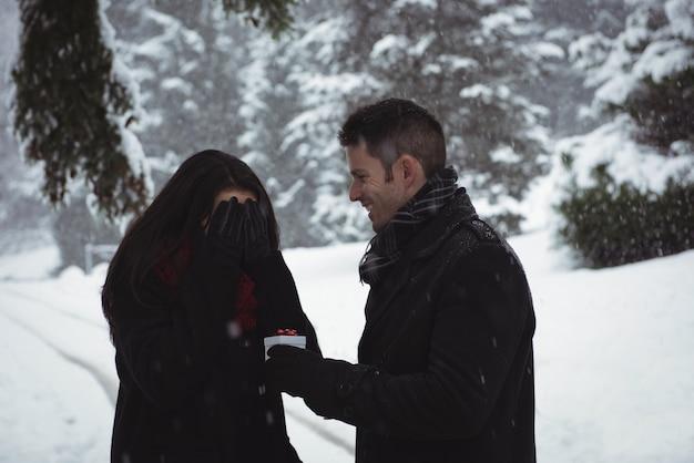 Kobieta zasłaniająca oczy, podczas gdy mężczyzna daje prezent niespodziankę w lesie zimą