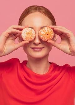 Kobieta zasłaniająca oczy pomarańczami