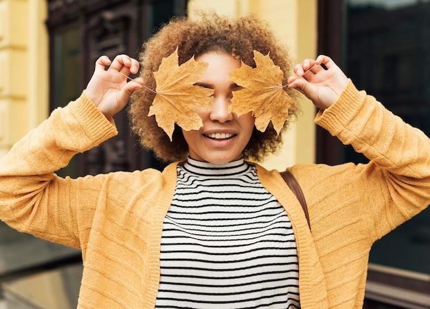 Kobieta zasłaniająca oczy suchymi liśćmi