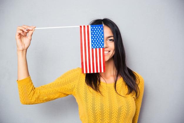 Kobieta zasłaniająca twarz amerykańską flagą