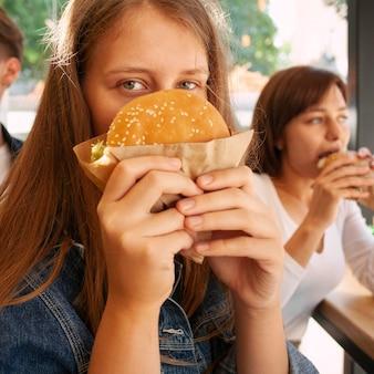 Kobieta zasłaniająca twarz burgerem