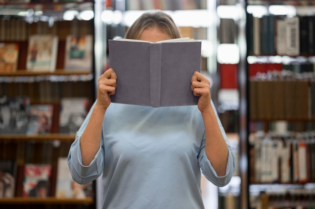 Kobieta zasłaniająca twarz książką