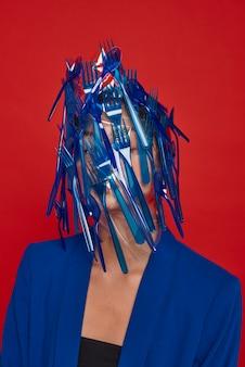 Kobieta zasłaniająca twarz niebieską plastikową zastawą stołową