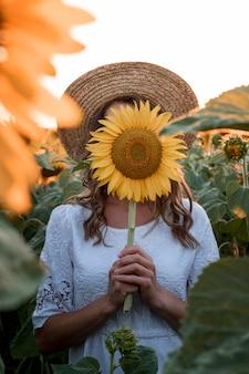 Kobieta zasłaniająca twarz słonecznikiem