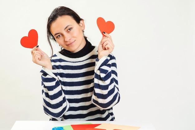 Kobieta zaślepiona wielką miłością. młoda kobieta trzyma czerwone serca na oczy i uśmiecha się. bądź moją walentynką.