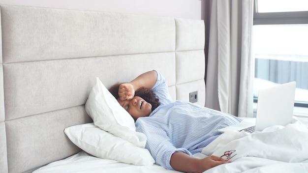 Kobieta zasnęła, oglądając filmy online na laptopie w łóżku