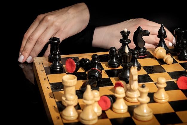 Kobieta zastanawia się nad kolejnym ruchem w grze w szachy siedząc przed starą drewnianą szachownicą z losowo ułożonymi pionkami