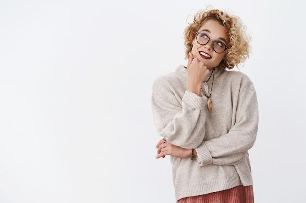 Kobieta zastanawiająca się, co zamówić na obiad, przypominająca lokalne restauracje, trzymająca rękę na brodzie i patrząca w lewy górny róg sennie i zamyślona z lekkim słodkim uśmiechem w hipsterskich okularach i swetrze.
