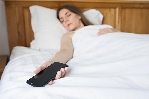 Kobieta zasypiająca po spędzeniu czasu na telefonie