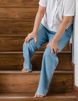 Kobieta zatrzymuje się na odpoczynek i opiera się o ścianę dla wsparcia, podczas gdy nie może wchodzić po schodach z mrowiącymi nogami. pojęcie zespołu guillain-barre i choroby zdrętwiałych nóg lub efekt uboczny szczepionki.