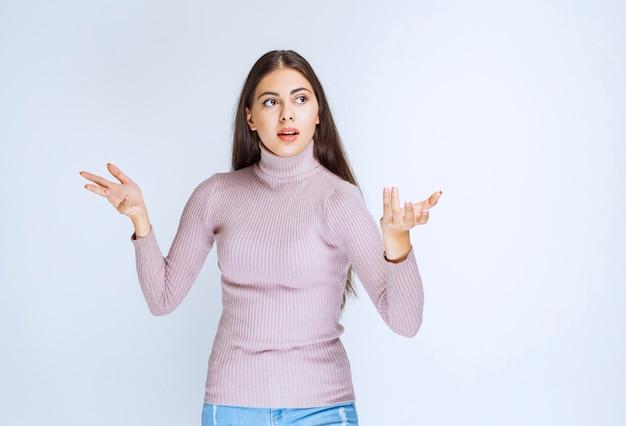 Kobieta zauważająca i przedstawiająca kogoś ręką gestykuluje.