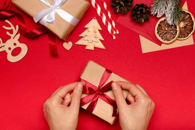 Kobieta zawijająca prezenty świąteczne z czerwoną wstążką na czerwonym tle, koncepcja bożego narodzenia.