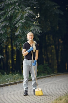 Kobieta zbiera liście i czyści park