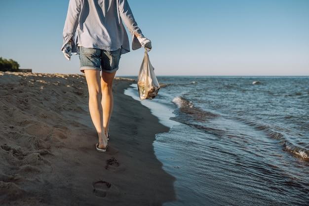 Kobieta zbiera plastikowe śmieci na piaszczystej plaży nad morzem. rozlane śmieci na plaży. koncepcja zanieczyszczenia środowiska.