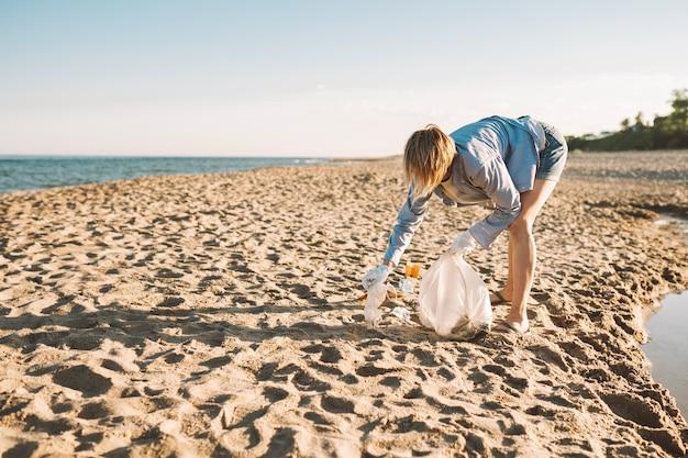 Kobieta zbiera plastikowe śmieci na piaszczystej plaży nad morzem rozlane śmieci na plaży p...