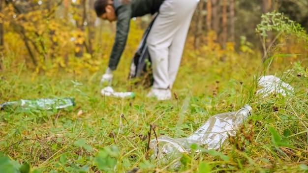 Kobieta zbiera śmieci w czarnej torbie w lesie z bliska.