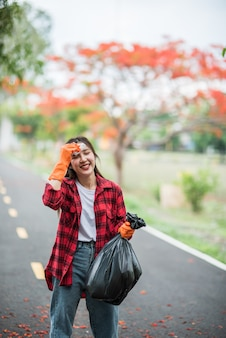 Kobieta zbiera śmieci w czarnej torbie.