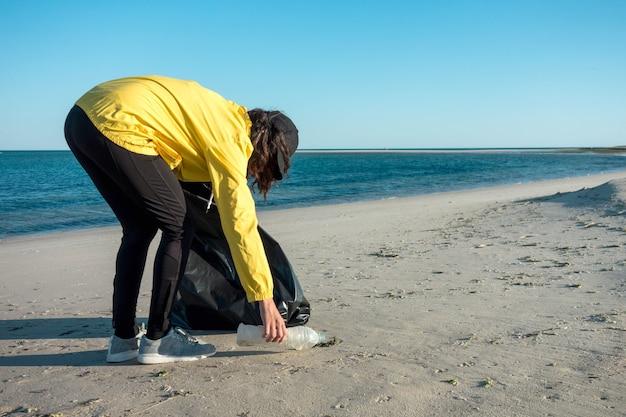Kobieta zbierając śmieci i tworzywa sztuczne sprzątając plażę workiem na śmieci. ekologiczny działacz wolontariuszy przeciwko zmianom klimatycznym i zanieczyszczeniu oceanów.