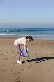 Kobieta zbieranie śmieci i tworzyw sztucznych, czyszczenie plaży
