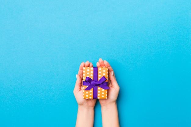 Kobieta zbroi trzymać prezenta pudełko z barwionym faborkiem na błękita stołu tle, odgórnego widoku i kopii przestrzeni dla ciebie, projektuje