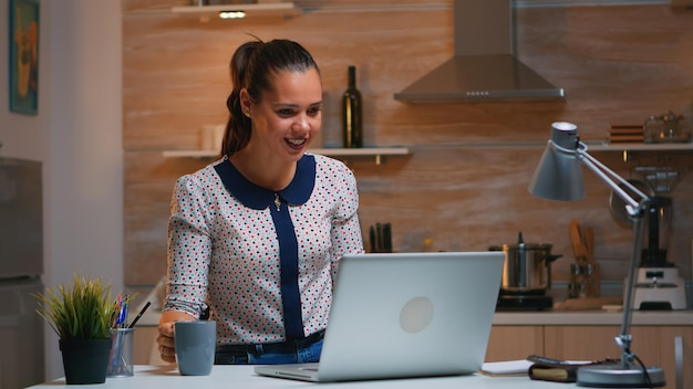 Kobieta zdalnego przedsiębiorca o wideokonferencji z kolegami za pomocą laptopa siedząc w kuchni późno w nocy. zajęty pracownik przy użyciu nowoczesnych technologii sieci bezprzewodowej robi nadgodziny do pracy.