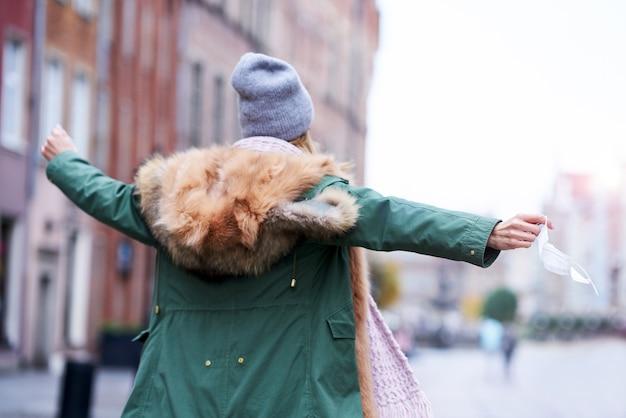Kobieta zdejmująca maskę w mieście
