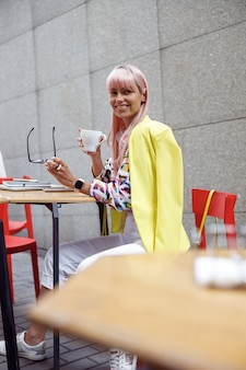 Kobieta zdejmująca okulary i uśmiechająca się do kamery z kawą