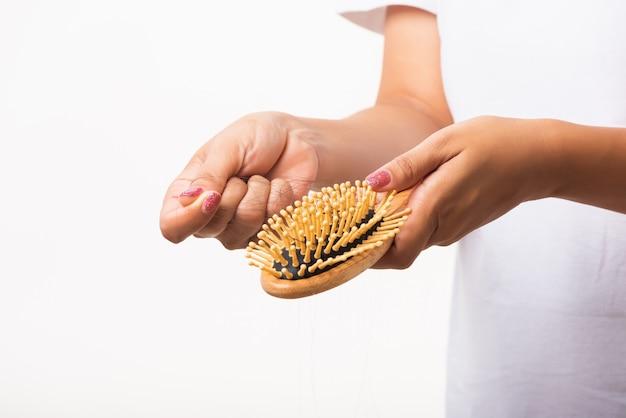 Kobieta zdejmująca włosy ze swojej szczotki