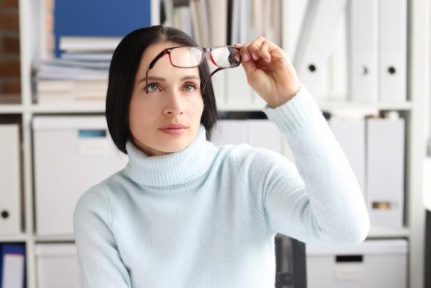 Kobieta zdejmuje się i patrzy na okulary siedząc w miejscu pracy