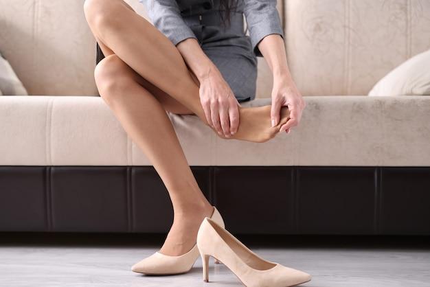 Kobieta zdjęła buty i rozmasowała zmęczone nogi. szkoda obuwia damskiego dla koncepcji zdrowia