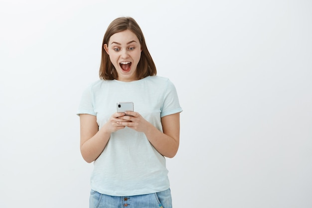 Kobieta zdumiona jak w niebie z otrzymanej wiadomości. entuzjastyczna śliczna dziewczyna w koszulce uśmiechnięta radośnie, triumfująca po dobrych wiadomościach, czytająca ciekawy artykuł w smartfonie, wpatrująca się w ekran telefonu komórkowego
