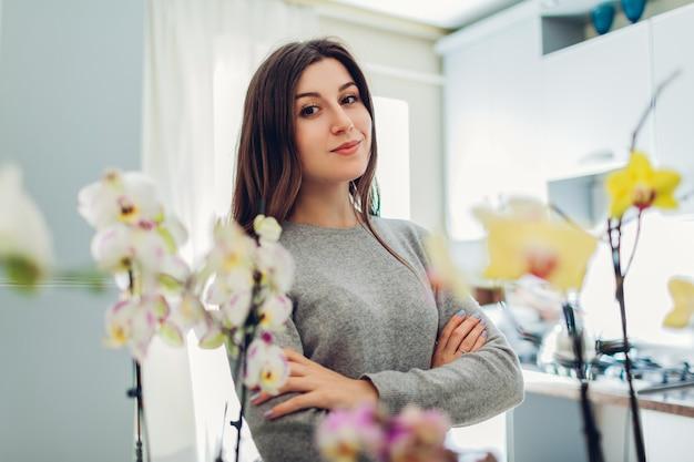 Kobieta ze skrzyżowanymi rękami jest dumna ze swoich storczyków w kuchni. gospodyni zajmująca się domowymi roślinami i kwiatami.