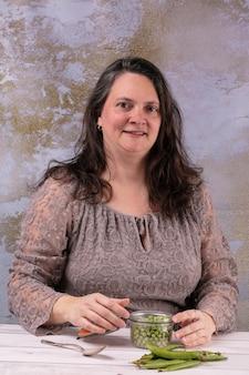 Kobieta ze słojem surowego groszku